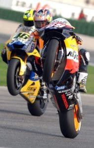 Nicky Hayden and rival Valentino Rossi wheelie in practice.