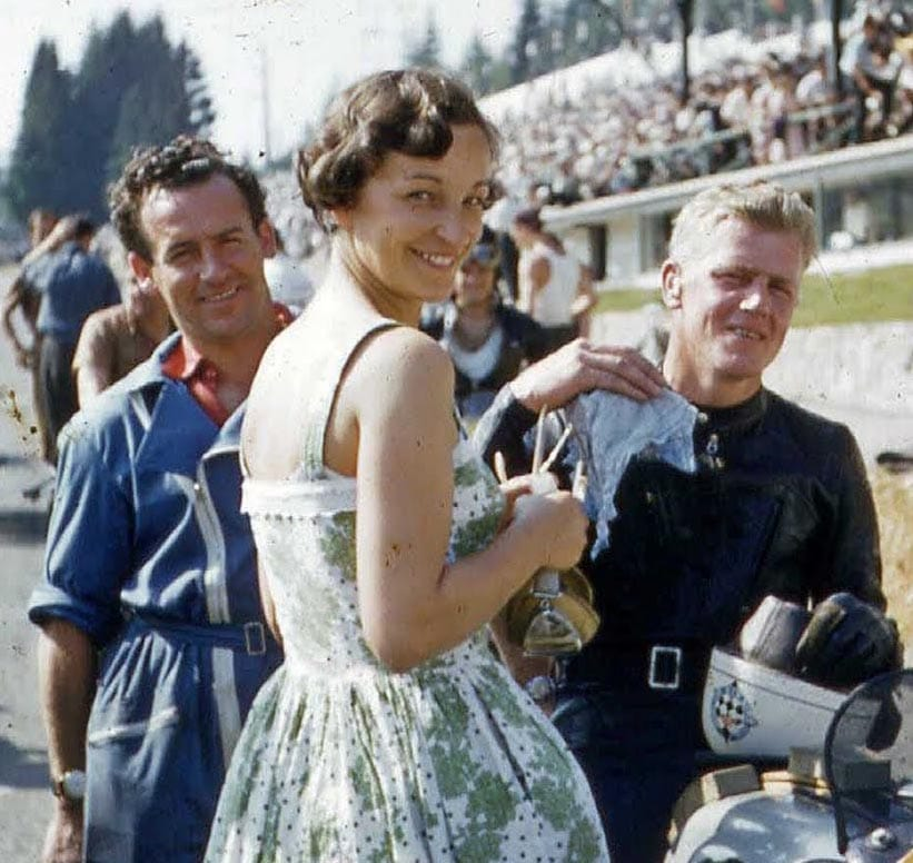 Grid girls have always performed a function in Grand Prix going back to the early days. Here a gal holds on to the rider's helmet while said rider wipes his sweat with a filthy rag. He lives for eternity knowing that he raced motorcycles while wearing a belt.