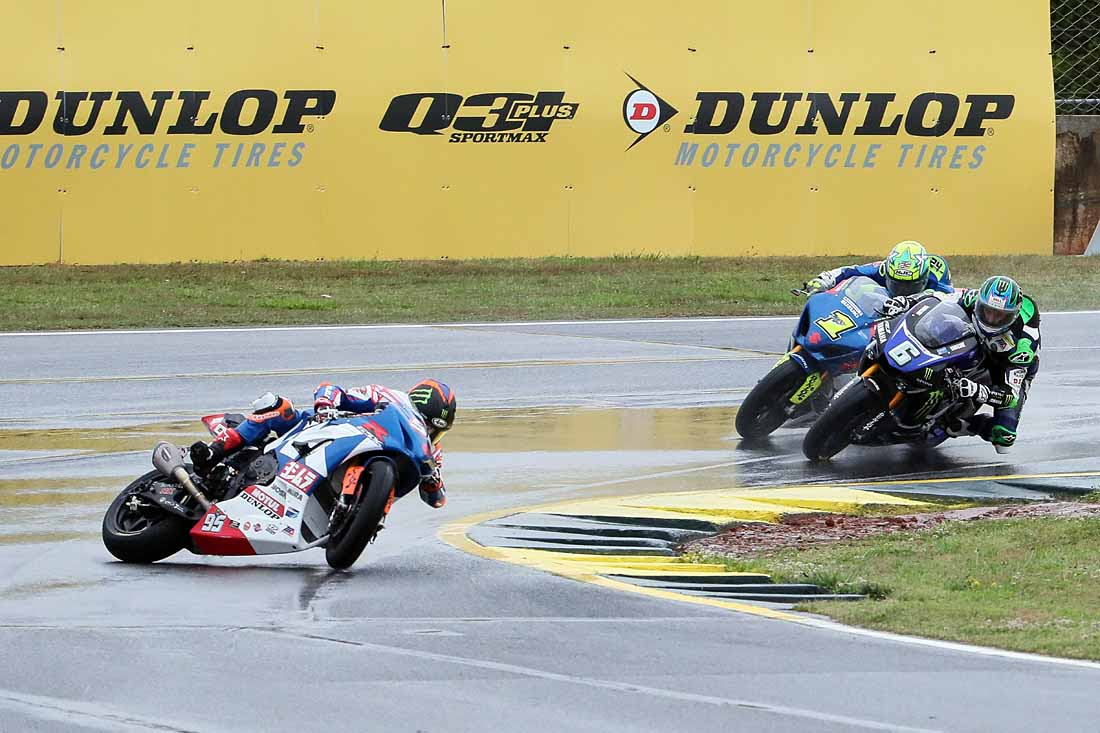Suzuki's Roger Lee Hayden mid-crash as Elias charges past the Yamaha.