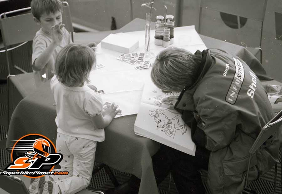 Kim Bayliss and kids coloring in the Ducati Corse hospitality unit, somewhere in Europe, 2000.