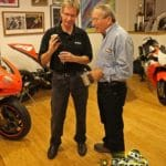 Eddie Lawson, who now drives race cars for Martin Adams, shows Mert Lawwill his phone.